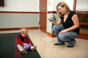 Woman Recording Toddler with Ball
