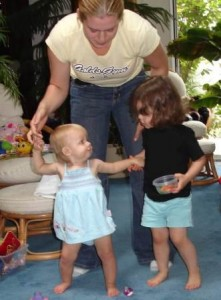 Woman Holding Hands of Two Toddlers