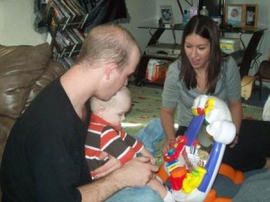 Two Adults Playing with Child on Floor