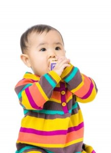 Baby Holding Toy to Mouth