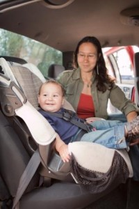 Smiling mother looks at toddler sitting in car seat and smiling