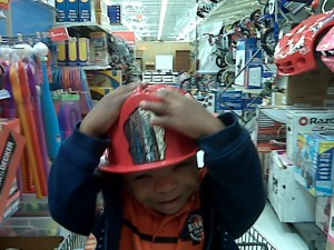 Toddler holds fireman's hat on his head