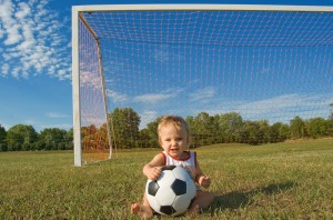 baby sitting in soccer goal with hand on soccer ball
