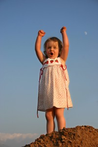 little girl on top of dirt hill raises her arms and yells