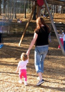 Woman holding toddler's hand as they walk through a playground