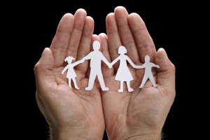 Hands hold paper cut out of a family