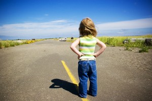 Toddler with hands on her hips looks down a long road
