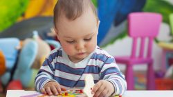 Toddler playing with a wooden puzzle