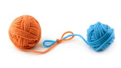 Two balls of yarn of different colors are tied together