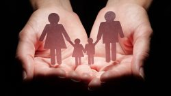 Hands hold a paper cutout family