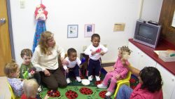 Adults and toddlers during circle time.