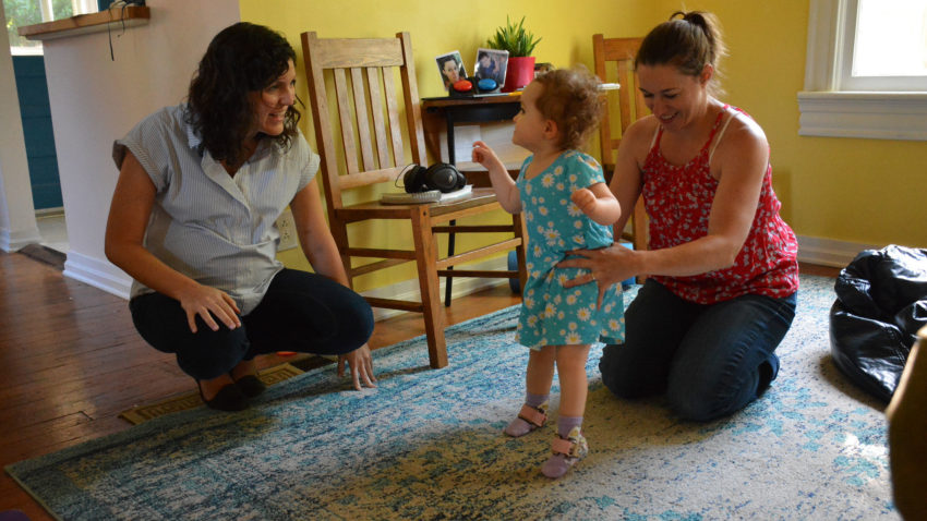 Mother and early interventionist are helping toddler learn to walk